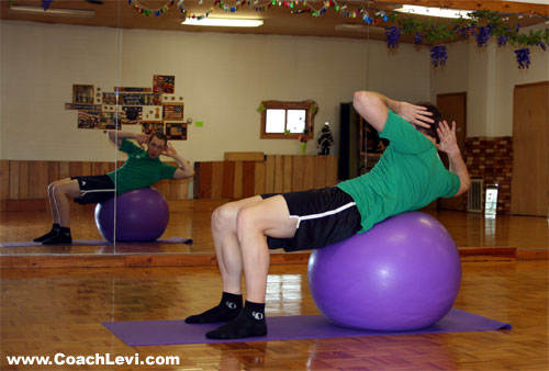 coach performing the twisting ball crunch ab exericse