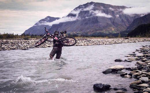 mountain biker walking through stream