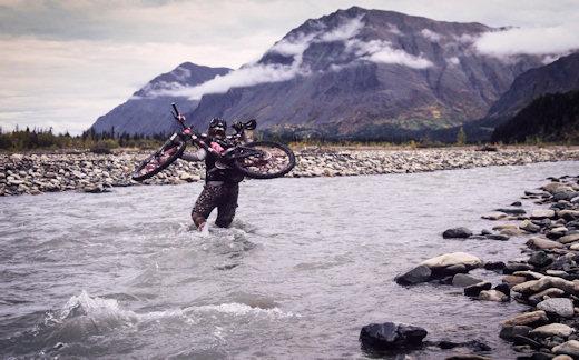 mountain biker walking through stream