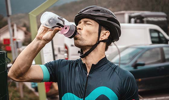 cyclist drinking a sports drink from his water bottle