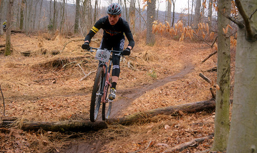 mountain bike racer hopping small log