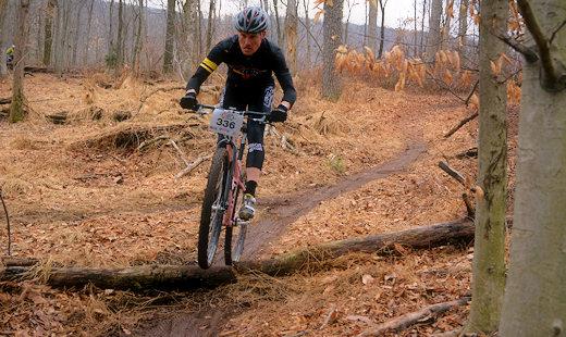 mountain bike racer hopping small log