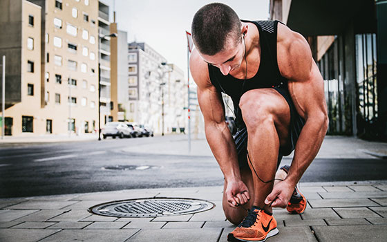 fit and muscular man lacing his running shoes