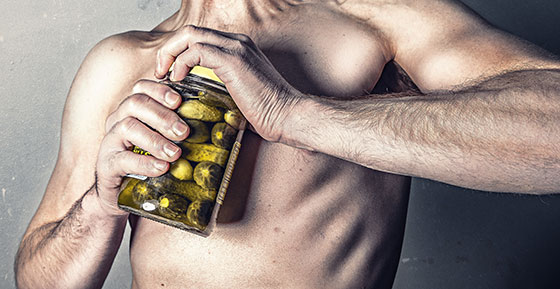 male athlete opening a jar of pickles