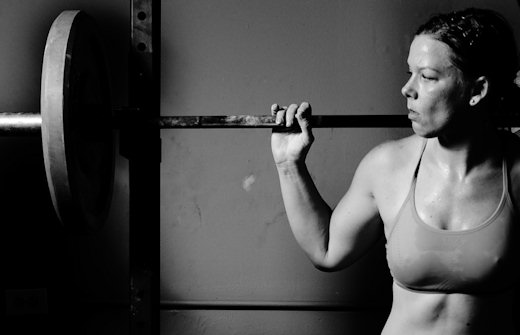 woman powerlifter at squat rack