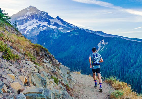 ultra runner on narrow mountain trail